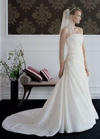 Taffeta draped A-line gown with beaded lace appliques on bodice and skirt.   Chapel train. Available in limited stores in Ivory/Champagne.  Fuly lined. Back zip. Imported Polyester. Dry Clean.  To preserve your wedding dreams, try our Wedding Gown Preservation Kit.
