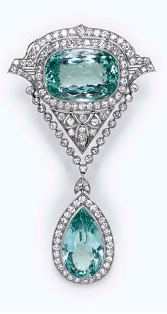 A BELLE EPOQUE AQUAMARINE AND DIAMOND BROOCH  Suspending a pear-shaped aquamarine, within a circular-cut diamond surround, accented by a circular-cut diamond foliate link, from a diamond collet chain, to a cushion-cut aquamarine, within a pavé-set diamond plaque of geometric design, mounted in platinum, circa 1910