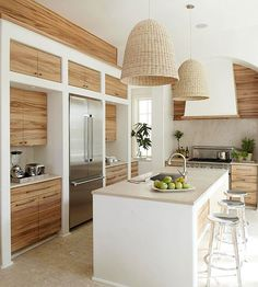 Two oversize pendant lights hang above this island and enhance the ambience of the room. The woven wicker shades contrast with the kitchen's sleek-lined aesthetic, and they also blend well with the stone flooring and the rustic wood grain on the cabinetry./