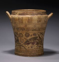 CORINTHIAN POTTERY PYXIS  Of unusual form, nearly cylindrical, faintly waisted, with rounded shoulder and broad mouth. Decorated with a central frieze of three dolphins amid rosettes, bordered by a checkerboard band. Above, a band of rosettes and a band with trios of vertical zigzags two applied canted handles at the shoulder. Very rare type.  Later Middle Corinthian, ca. 575 BC