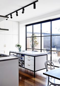 Steel-frame black and white kitchen: floor-to-ceiling steel-frame windows, steel-frame island with 80mm-thick Arabescato marble benchtop, white cabinetry with gold handles, white Thonet bentwood dining chairs, timber floorboards, black spotlights on black ceiling track