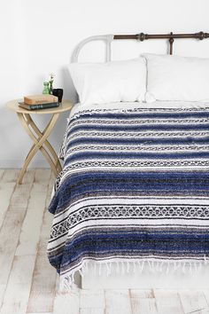 This photograph shows just how little you need to create a really great fresh bedroom look. The bleached floorboards, classic iron bedstead and  artisan timber side table all play a supporting role to the indigo striped perfection of a simple Mexican throw.