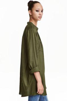 Camisa larga: Camisa larga en viscosa suave. Modelo con bolsillos superiores con solapa y botón, bajo redondeado y espalda algo más larga.