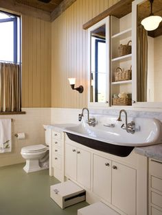 Trough sink, flat-panel cabinets, beige cabinets, beige tile, brown walls and a two-piece toilet.