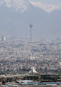Two Symbols of Tehran - Azadi Square in front and Milad Tower behind