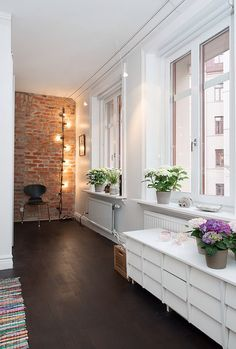 Brick wall, white walls, dark floors