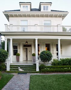 Southern style home, probably on the Carolina coast, with double front door, dormers, and covered porch with white columns and gracious entrance stairway.