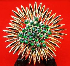SoVintageous is offering this fabulous vintage gold-tone sunflower brooch with sparkling, faceted emerald green rhinestones.  The layered petals give wonderful depth, while the dome-shaped, bezel-set,