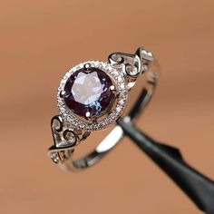 It is a lab created alexandrite ring. The main stone is 7mm*7mm round cut. weight about 1.84 carats.Its stunning and lovely! The basic metal is sterling silver and plated with rhodium. To change the metal to a solid gold (white/rose) or platinum is also available, please ask for a quotation if you want. You can also go to my shop Home for more elegant rings: https://www.etsy.com/shop/godjewelry?ref=hdr_shop_menu Customization is always welcome and please feel ...