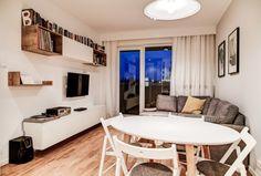 Salon w nowoczesnej aranżacji. Drewniana podłoga oraz białe ściany tworzą idealną bazę pod dodatki, czyli książki, interesujące grafiki w ramkach i kolorowe poduszki. W salonie znalazło się również miejsce na stół o okrągłym kształcie i komplet krzeseł.