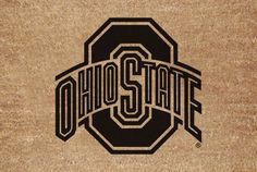 """Ohio State Flocked Door Mat by The Memory Company. $28.95. Size 29.2"""" x 19.5"""". Greet your guests in style with this NCAA® door mat from The Memory Company®. It features a flocked coir fiber construction, boasts a skid-resistant rubber bottom, and is decorated with the team logo."""