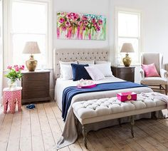 The bright painting above this tufted bed makes this bedroom a delightful and happy place to be