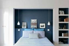 The deep blue feature wall behind the bed creates the illusion of a bedhead