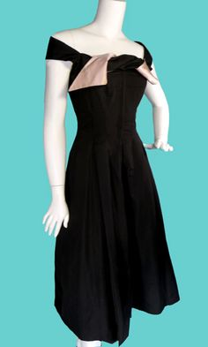 "Nettie Rosenstein  Little Black Dress  From the designer who promoted the ""little black dress"" and knew how to turn simplicity into extraordinary, comes this exceptional 1950's evening gown.  The bateau neckline drapes across the shoulders and has a unique sash lined in pink satin that snaps onto the bodice."