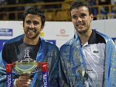 Janko Tipsarevic of Serbia (left) holds the winner's trophy after the final match against Roberto Bautista Agut of Spain (right). AP