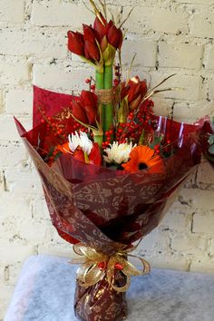 Here's a good start to the very busy Christmas period, 2 stunning big hand-tied bouquets of amaryllis, ilex berries, white blooms, red anthurium, orange gerbera, eucalyptus, red naomi roses, cherry brandy roses, blue eryngium and gold skimmia. All wrapped in luxurious Christmas cellophane and tied with beautiful gold bows! These are the first of many many more being sent out today. #reidsflorists #Christmas #Christmasflowers