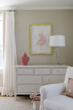 source: Finnian's Moon Interiors    girl's nursery design with tan walls paint color, white curtains window panels with coral pink Greek key trim, white dresser, coral pink pierced carthage lantern, jute rug, yellow & pink art, Arteriors Cooper Silver Leaf Iron Lamp and white glider with pink pillow.