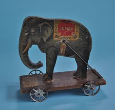 This is a wonderful toy, probably from 1910-20s. American company. A wooden platform with cast metal wheels, the jointed elephant is wood...