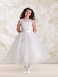 Sleeveless satin, tulle and lace tea-length A-line dress, organza overlay bodice features an illusion jewel neckline and scattered hand-beading, satin waistband with center back bow and back covered buttons, full gathered multi-layer tulle overlay skirt accented with scattered beaded lace appliqués and wire scalloped hem, ideal for First Holy Communion. Sizes: 2 – 14 Colors: …