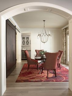 This Currey Chandelier looks amazing with these red chairs and ties together perfectly with the curtains!