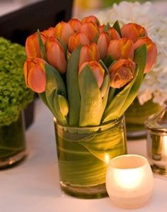 Tulips are a quintessential spring flower and this simple vase of tulips (with ti leaf wrapped inside the vase). Placing a tea light next to it gives the flowers a warm glow.