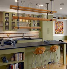 I see some kind of book storage, or wine storage on the living room side with 2 counter height stools. ceiling mounted shelves kitchen - Google Search