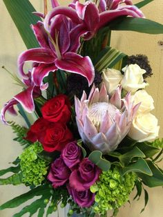 Close up of a contemporary arrangement. Protea king, roses, lilies, hydrangeas, trachelium. Pink, burgundy, green, red and white.