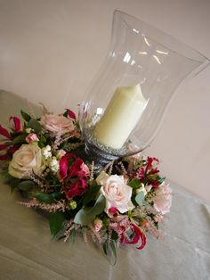 wedding table centre. hurricane vase. wreath around the base. Sweet Avalanche roses with astilbe, spray roses and gloriosa lilies