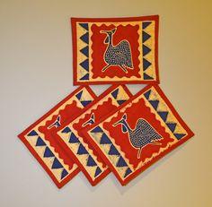 """Blue Guinea Fowl Red Placemats"" Zimbabwe Textiles. Blue and yellow guinea fowl, red, blue, yellow placemats. Setof4 hand printed Africanplacemats. TheseplacematsarehandprintedbyZimbabweanwomenwhoworkfromhome. TheirwaresarethensoldattheAvondaleMarketinHarare, Zimbabwe. 30% of net profits go back to 3 Zimbabwe charities."