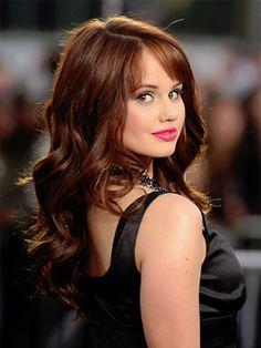 Long, curled, rich red hair and fair skin.