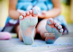 Little girls feet covered with chalk.