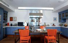 """A madeira de demolição no piso e as cores alegres nos móveis reforçam a ideia de que a cozinha é um espaço também para receber neste apartamento. """"Os tons de azul e laranja deram jovialidade ao espaço"""", diz a designer de interiores Marina Linhares"""