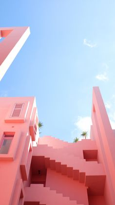 The pink exterior of a uniquely built building.