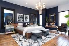 This master bedroom has modern art, a dark wall color, a shag rug and gold accents to create the ultimate resting space. Texture and pattern in rugs, throws and contemporary art add drama. Navy Master Bedroom, Dark Wood Bedroom, Blue Bedroom Walls, Bedroom Paint Colors, Modern Bedroom, Navy Gold Bedroom, Masculine Master Bedroom, Eclectic Bedrooms, Master Master