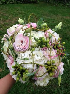 Wedding garden bouquet of white hydrangea, pink lisianthus, green hypericum berries, caged with curly willow branches.