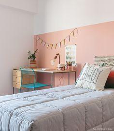Quarto de adolescente tem meia parede pintada de rosa e escrivaninha de madeira e ferro.