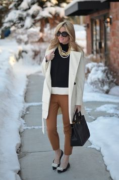 Black cardigan, white undershirt, tan pants, black flats, and off white mid-length jacket