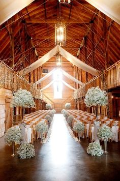 Bundles of white flowers and branches wrapped in lights illuminate the path for the bride and groom at this rustic wedding ceremony.