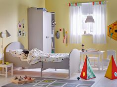 Childrens bedroom with yellow walls and light grey extended bed and wardrobe.