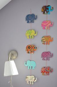 DIY Elephant (or anything u want!!) hanging cutouts. Find a stencil online and trace it onto different colored scrapbook paper. Then tape, glue, or staple onto a string.