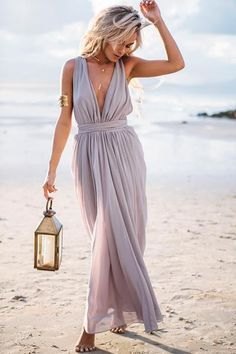 The Gown is an amazing floor-length maxi dress in grey featuring a draped style skirt which gathers at the waist and a plunge neckline. The back featured draped, pleated detailing with a tie up sash b