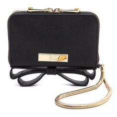 Zac Posen Wrislet Sophisticated saffiano calfskin composes this ZAC Zac Posen phone wristlet. Gold-tone hardware and a signature bow details the exterior. The wraparound zip opens to a leather-lined interior with a phone compartment, 4 card slots, and 2 bill slots. Snake chain wrist strap. Dust bag included.  Leather: Calfskin. Imported, China.  MEASUREMENTS Height: 4in / 10cm Length: 6.5in / 16.5cm Depth: 1.5in / 4cm Zac Posen Bags Clutches & Wristlets