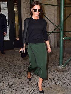 Victoria Beckham struts in a hunter green skirt and sunglasses