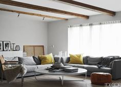 The living room of a farmhouse on Sweden's Bjare Peninsula, which was renovated by designer Lisette Bramsell for her family; the sofas are by Claesson Koivisto Rune, the cocktail table and console are custom made, the pouf is Egyptian, and the curtains are of a Kvadrat linen; the floor is lined with Douglas pine by Dinesen, and the beams are original to the house.