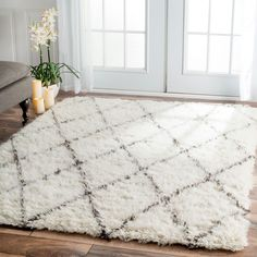 This hand-tufted wool area rug features an elegant design. This soft and plush area rug was meticulously handcrafted to create a luxurious boldness and softness under foot.