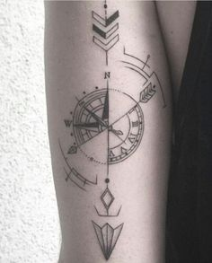 Compass tattoo with arrow on forearm.