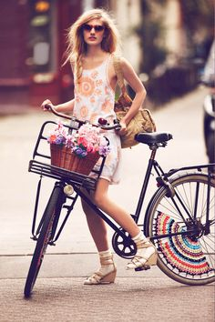 """Girls on Bikes – Free People enlists a mix of models and ""real girls"" to wear the latest styles as they ride their bikes in the streets of Amsterdam. Guy Aroch captures the girls in flirty and practical spring pieces including sheer dresses, casual denim, fringe jackets and floral prints. Free People will also sell a limited edition collection of bike apparel for the month of January; the line features hand-painted bike seats, embossed handlebar grips and crotchet skirt guards."""