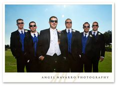 groom: white vest & tie with black suit & red boutonniere; groomsmen: navy vests & ties with black suits & white boutonnieres