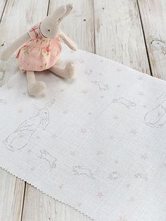 Rabbit All Star Fabric A linen fabric featuring grey outlined rabbits with their playful young amongst pink stars.