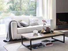 Sofá en color blanco delante del ventanal y mesa de centro en madera y metal